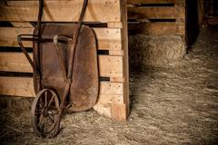 Aged rusty barrow in the wooden farm barn. agriculture theme. Kuvituskuvat