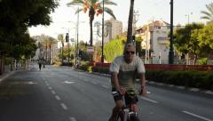 Gray-haired man rides bicycle in front of the camera - stock footage