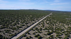 Aerial - Fying over a long, straight road, cutting through green landscape Stock Footage