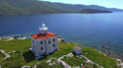 Aerial - Solitude lighthouse on a small island with crystal clear blue water - stock footage