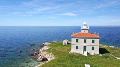 Aerial - Solitude lighthouse with green field and clear blue water around Stock Footage