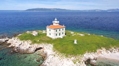 Aerial - Solitude lighthouse on a small island with turquoise water around - stock footage