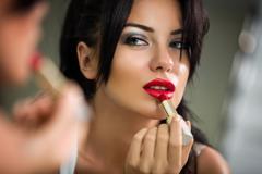 Woman applying lipstick looking at mirror Kuvituskuvat