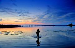 man exiting water.lake.sunset. - stock photo