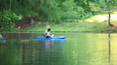 Boy Paddles with his Hand as He Sits on Float in Pond Stock Footage