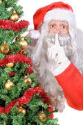 santa claus showing hush gesture with finger on lips - stock photo