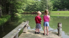 Young Children Fishing off a Dock with Beautiful Pond in Background Stock Footage