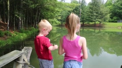 Young Boy and Girl Reels in their Fishing Lines Stock Footage