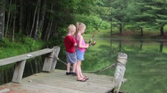 Children Fishing off a Dock on a Pond Stock Footage