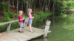 Young Boy Plays with Fishing Reel as Girl Fishes  (HD) Stock Footage