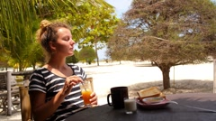 Young Woman Having Breakfast in Restaurant on Beach. Arkistovideo