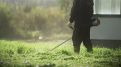 Man Cutting Overgrown Grass with Lawn Mower Stock Footage