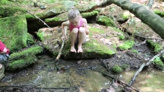 Young Girl Sits on a Rock and Pokes at Muddy Stream with Stick Stock Footage