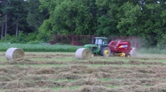 Stock Video Footage of Round Hay Baler Scoops up Dry Hay for Baling