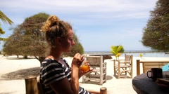 Girl Enjoying Morning Sun and Juice in Beach Cafe at Sea. - stock footage