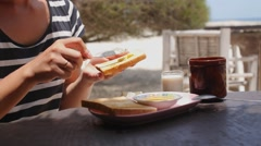 Woman Eating Toasts with Honey for Breakfast at Beach Cafe. Stock Footage