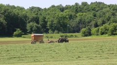 Stock Video Footage of Farm Tractor Pulls Cart Left to Right at Alfalfa Harvest