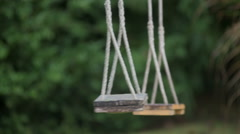 A swing-set swaying against a green foliage background Stock Footage