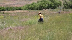 Woman Dressed as an Old West Settler Walks Across a Grassy Prairie Field - stock footage