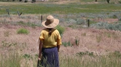 Woman Dressed as an Old West Settler Watches Over a Grassy Field - stock footage