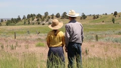Cowboy and Cowgirl Embrace Each Other in Open Prairie - stock footage