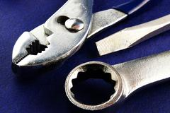 screwdriver, wrench and pliers closeup on blue textured background - stock photo