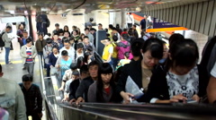 Passengers walk out of train and on to the escalator in a subway in Beijing Stock Footage
