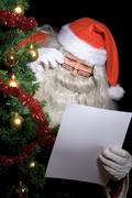 Santa claus reading wish list beside christmas tree Stock Photos