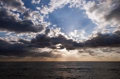 Sun shining through clouds Stock Photos
