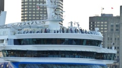 Tourists on cruise ship's top level deck with buildings in background Stock Footage