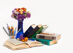 Teacher's day! (composition with spring flowers in a blue vase, old books, gl Stock Photos