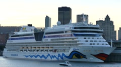 Small yacht cruising in front of giant cruise ship in city port Stock Footage