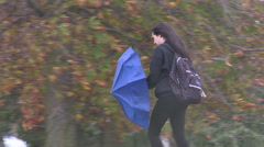 People running for cover in wild rain and wind storm on campus Stock Footage