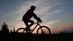 Cyclists continues at sunset Stock Footage