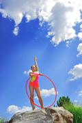 gymnast with hoops on a background blue sky.sporting exercises. - stock photo