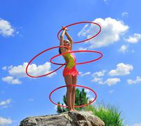 Gymnast with hoops on a background blue sky.sporting exercises. Stock Photos