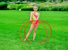 gymnast in a bright clothing with hoops on a green grass.sporting exercise. - stock photo