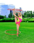 Gymnast in a bright clothing with hoops on a green grass.sporting exercise. Stock Photos