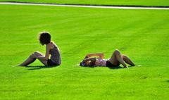 girls holiday-makers on a green grass.rest.day off. - stock photo