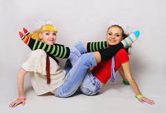 the merry girls of girl-friend are pampered on a grey background.hugging girl - stock photo