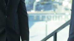 Good deal. Two confident businessman shaking hands in formalwear Stock Footage