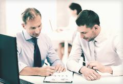 Businessmen with notebook on meeting Stock Photos