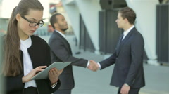 Business woman standing in the street while two businessmen shaking hands - stock footage