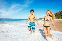 Attractive happy couple running and playing on beautiful sunny beach Stock Photos