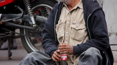 A homeless man sits on the curb in a small town in Mexico Stock Footage