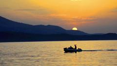 Fishing boat moves through the water at sunset. Stock Footage