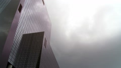 Commercial office building threatened by dark stormy rainclouds - stock footage