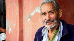 A old Mexican man poses for the camera down by the fishing docks - stock footage