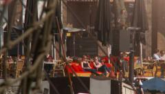 Rack focus from old ships to girls on terrace on sunny spring day Stock Footage