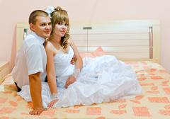 married couple on a bed.wedding.groom and fiancee. - stock photo